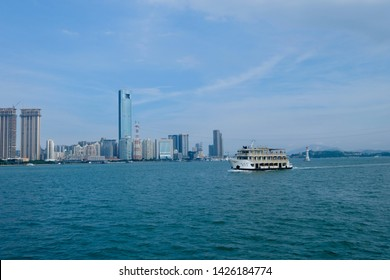 Xiamen. Fujian/China-June 2019: ferry ship on blue sea water transferring tourists from Xiamen to Gulangyu Island. Modern buildings and blue skyline as background. Xiamen is a famous tourist city