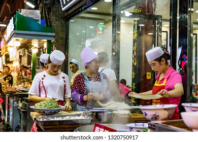 XIAN, CHINA -1 AUGUST 2017- Night view of street food vendors making and selling noodles in the Muslim Quarter area of Xi'an, also known as Beiyuanmen Muslim Market.