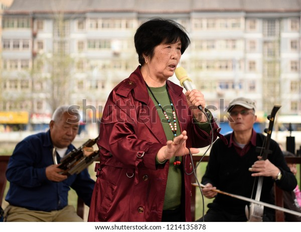 XI'AN, CHINA - APRIL 11 2017:  An elderly chinese woman is seen singing old folk songs in a park on April 11, 2017 in Xi'an, China