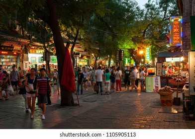 Xian, China - August 6, 2012: People walking in a street of the Muslim Quarter in the city of Xian at night, in China, Asia