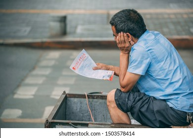 Xian, China -  July 2019 : Chinese man reading information advertising leaflet while sitting inside a wheeled trolley