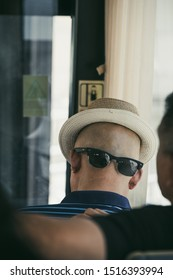 Xian, China -  July 2019 : A chinese man wearing his sunglasses on the back of his shaved head with a hat that gives the illusion of a face, public transport