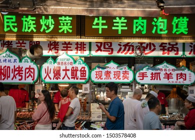 Xian, China -  July 2019 : Colorful and brightly illuminated and lit neons and shop boards in the popular street food district called Muslim Quarter