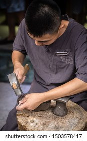 Xian, China -  July 2019 : Man using hammer to make crafts on the street market in the Muslim Quarter, Xian town, Shaanxi Province
