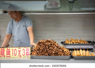 Xian, China -  July 2019 : Meat, snacks, calamari and fried baby octopus vendor selling food on the street in the Muslim Quarter