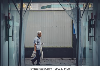 Xian, China -  July 2019 : Old chinese man walking on a street in Xian, photographed from the inside of a shop