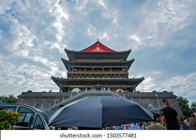 Xian, China -  July 2019 : Person with an umbrella in front of the landmark Drum Tower in the city Xian, Shaaxi Province