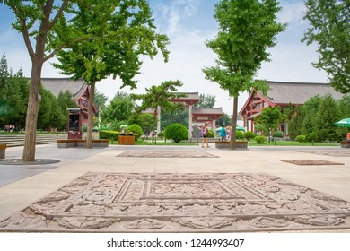 Xian, China - July 25, 2010: Local people walkin in Dayan Pagoda Square. Dayan Pagoda Square has many featured sculptures and gardens around the pagoda and temple.