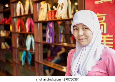 XIAN, CHINA - JUNE 20: Young Hui woman sells shoes at famous Muslim Street on June 20, 2012 in Xian. Hui people are a Muslim ethnic minority in Xian and run a lively market at Muslim Street.
