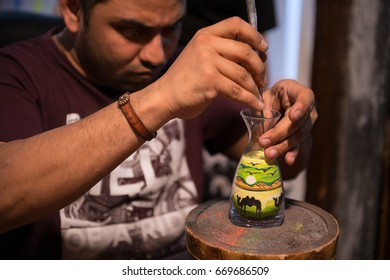 Xi'an, China - May 25, 2017: Sand artist designing colorful sand bottle