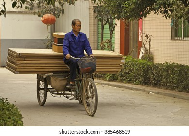 Xian, China, September 26, 2009: Unidentified man using a tricycle  for transporting building materials in a rural area of China.