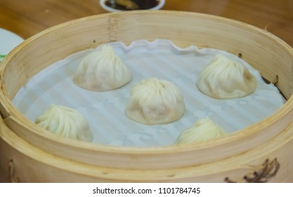 Xiao Long Pao in bamboo steamer, Chinese cuisine, soft focus
