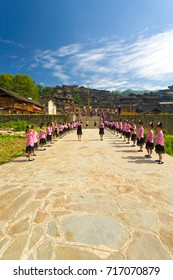 Xijiang, China - September 15, 2007: Cute adolescent girls prepare for festival ceremony in traditional pink clothes at the town square of beautiful ethnic Miao village of Xijiang