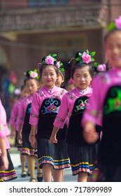 Xijiang, China - September 15, 2007: Miao ethnic minority girls dressed in pink and black dress performing a dance at the Miao village of Xijiang, Guizhou, China