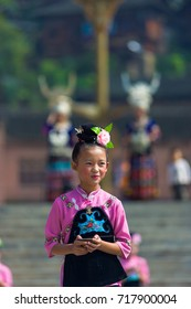 Xijiang, China - September 15, 2007: An Miao ethnic minority girl dressed in pink and black performing at a local festival at the traditional Miao village of Xijiang, Guizhou, China