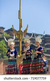 Xijiang, China - September 15, 2007: Three Miao women wearing full traditional festival regalia with silver horn headdress at town square in Xijiang ethnic minority Miao village, Guizhou, China