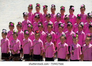 Xijiang, China - September 15, 2007: Cute adolescent Miao ethnic minority girls singing in pink festival costume at Xijiang ethnic minority Miao village, Guizhou, China