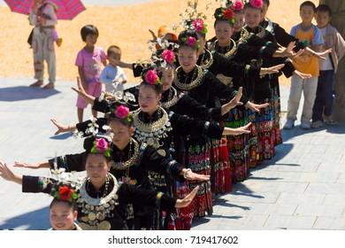 Xijiang, China - September 15, 2007: Line of Miao women dance wearing full traditional festival regalia and colorful costume at Xijiang ethnic minority Miao village, Guizhou, China