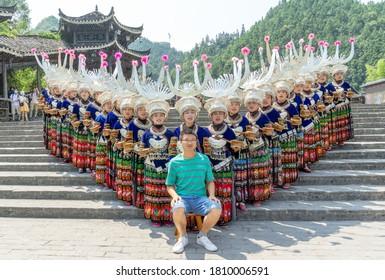 Xijiang, China - SEPTEMBER 2,2020: Miao women dancing in full traditional festival regalia and colorful costume with silver horn headdress in Xijiang ethnic minority Miao village, Guizhou, China