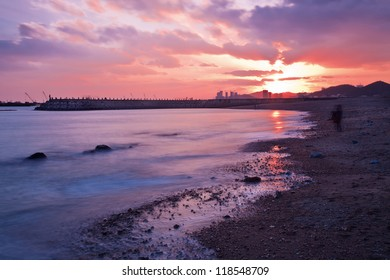 Xinghai Beach at a red colored sunset reflected in the sea, Dalian, China