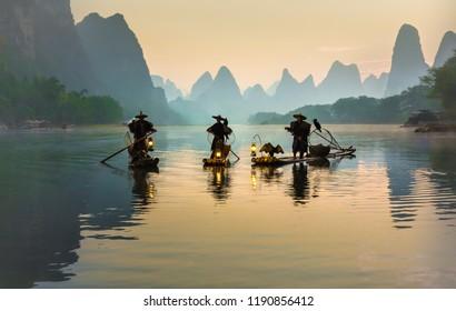 XINGPING, CHINA - OCTOBER 22, 2014: Cormorant fishermen on ancient bamboo boats with lighted lamps and cormorants - The Li River, Xingping, China