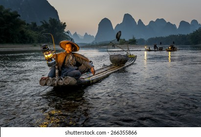 XINGPING, CHINA - OCTOBER 22, 2014: Cormorant fisherman on an ancient bamboo boat with a lighted lamp and cormorant - The Li River, Xingping, China
