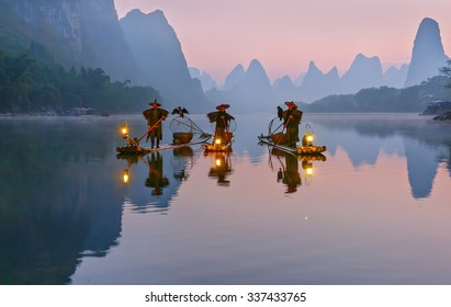 XINGPING, CHINA - OCTOBER 22, 2014: Cormorant fishermans stands on the ancient bamboo boat with a lighted lamps and cormorants in the sunrise - The Li River, Xingping, China