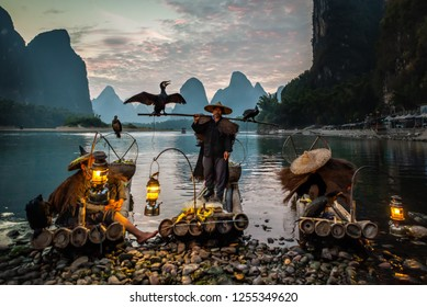 XINGPING, CHINA - OCTOBER 23, 2014: Cormorant fisherman on the ancient bamboo boat with a lighted lamps and cormorants - The Li River, Xingping, China.