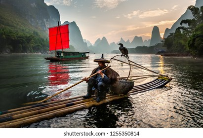 XINGPING, CHINA - OCTOBER 23, 2014: Fisherman stands on traditional bamboo boats at sunrise (boat with a red sail in the background) - The Li River, Xingping, China.