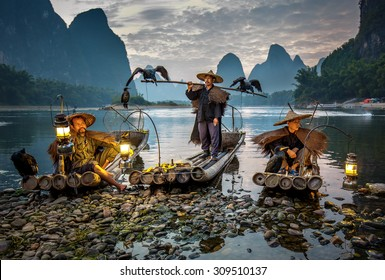 XINGPING, CHINA - OCTOBER 23, 2014: Cormorant fisherman on the ancient bamboo boat with a lighted lamps and cormorants - The Li River, Xingping, China