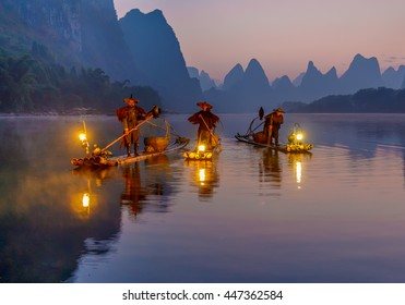 XINGPING, CHINA - OCTOBER 23, 2014: Three cormorant fishermen standing on traditional bamboo boats with lighted lamps - Li River, Xingping, China