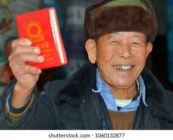 XINGPING, GUANGXI/CHINA - DEC 2, 2012: Old Chinese communist man with gold teeth wears an ushanka hat, waves his copy of Mao's Little Red Book and poses for the camera in his house, on Dec. 2, 2012.