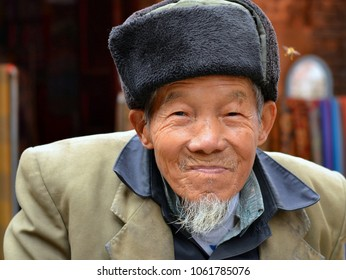 XINGPING, GUANGXI/CHINA - DEC 2, 2102: Old Chinese river fisherman wears a military-style ushanka hat and poses for the camera in front of his house, on Dec 2, 2012.