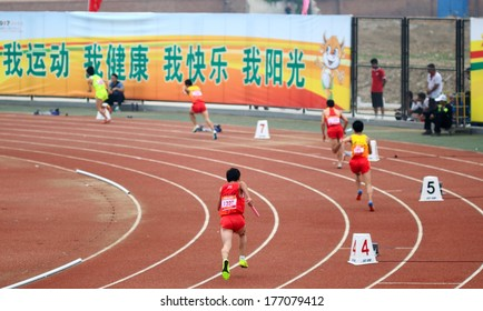 XINGTAI CITY, HEBEI PROVINCE, CHINA - June 2012: On June 1, 2012 Chinese University Games, four by one hundred in the game, players competitive, boldly, very exciting.