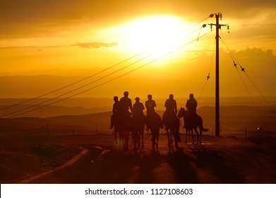 Xinjiang, China - June 10, 2018: a group of Kazakh young herdsmen are riding on horseback in the sunset, Tekes County, Xinjiang, China.