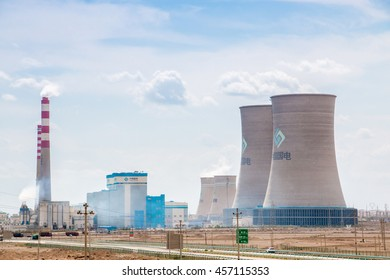 Xinjiang,China 09/03/2015 Chinese nuclear power plant with surrounding buildings in front of a blue cloudy sky in Xinjiang China
