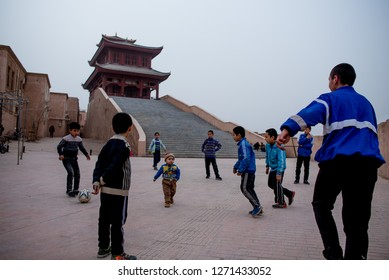 Xinjiang,China,January 1 2019- A group of uyghur children playing football in front of abandon temple in the Old City of Kashgar. Kashgar has majority of a muslim uyghur ethnic in China.