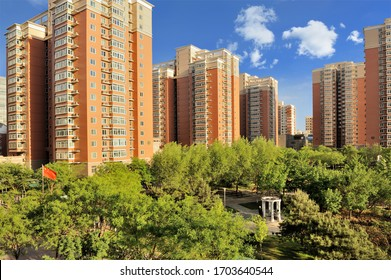 Xinkexiangyuan Housing Developments under Cloudy Sky with Trees and Chinese National Flag as Foreground in Zhongguancun Area, Haidian District, Beijing, China in July 2018
