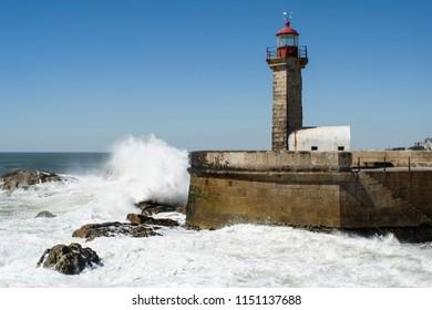 XIX century Felgueiras Lighthouse in Foz do Douro, near Porto, Portugal, with rocks below and waves smashing unto its base.