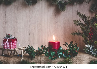 Xmas card. Candle and branches of a holly decoration with Christmas ornaments on a wooden frame