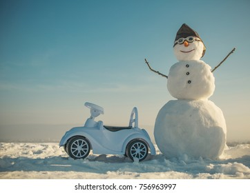 Xmas or christmas decoration, aviation. Happy holiday celebration. New year snowman in pilot hat and glasses. Christmas and transportation. Snowman in winter with toy car, travel and vaction.