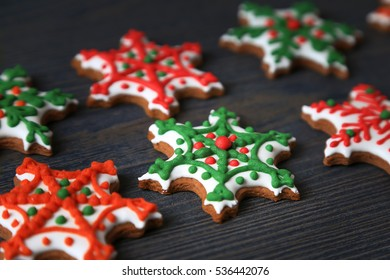 Xmas cookies in a shape of red and green snowflakes on a dark wooden background