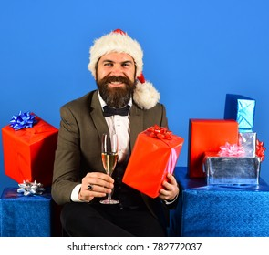 Xmas corporate party concept. Businessman with happy face holding boxes pile and drink. Santa in retro suit presents blue and red gifts. Man with beard holds present and champagne on blue background