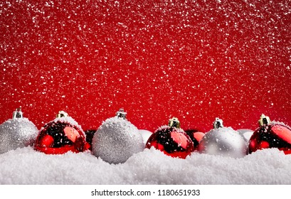 Xmas greeting card design and background. Red and silver baubles in snow on red backdrop, copy space