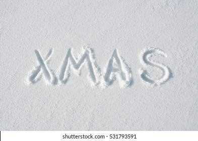Xmas letters handdrawn on flat snow surface. Nice horizontal holiday postcard, greeting card.