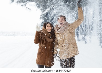 Xmas Morning. Happy Couple Throwing Snow Walking In Snowy Winter Forest Enjoying And Having Fun Outside. Free Space