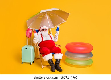 X-mas online tickets resort buy. Full body photo of white grey hair bearded santa claus sit chaise-lounge hold smart phone passport wear red sunglass cap isolated yellow color background - Shutterstock ID 1817144960