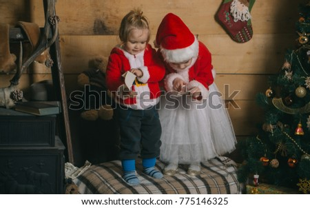5217d26ab Xmas party celebration, childhood Santa claus kid at Christmas tree.  Christmas happy children in red hat. Winter holiday and vacation. New year  small girl ...