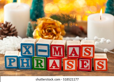 X-Mas Phrases Written With Toy Blocks On Christmas Card Background With Copy Space.