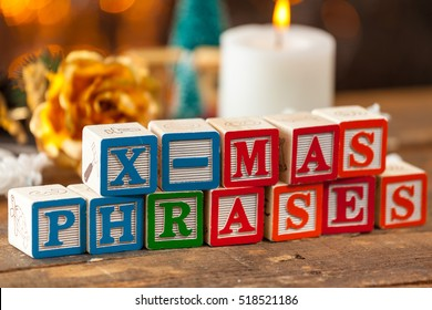 X-Mas Phrases Written With Toy Blocks On Christmas Card Background.